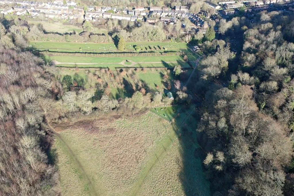 Overhead view of formal and woodland burial ground and adjacent chalkland meadow.  To the north are the housings along Bois Moor Road and Woodley Hill and woodlands to the East and West.